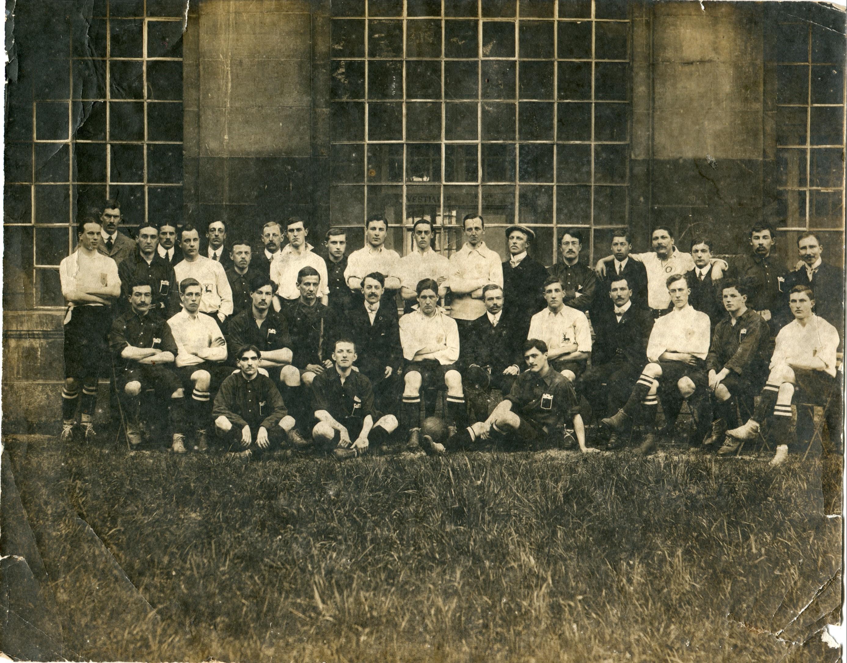 Les Anglais sont en maillots blancs (on peut reconnaître, floqués sur certaines poitrines, le cerf des armoiries du comté du Hertfordshire), tandis que les Caennais arborent une jolie chemise rouge aux armoiries de la Normandie. Curiosité : un membre de l'encadrement (4e en haut en partant de la droite) porte le maillot de l'équipe de France reconnaissable aux  deux anneaux rouge et bleu entrelacés de l'USFSA. Assis, encadrant les deux joueurs anglais du centre, le président du comité USFSA de Basse-Normandie, Albert Berger, le secrétaire Fernand Toullier et le vice-président Henri Françoise. Les onze joueurs caennais : En haut, De g. à d. : Vassel, Bourgeois, Délivré, Cossevin, Heuzé. Au milieu : Picard, Parat, A. Lesomptier. En bas : Vromet, E. Lesomptier, Jardin.